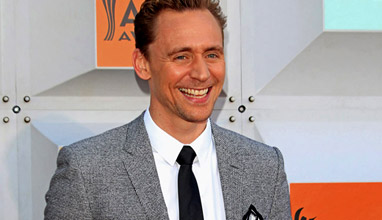 Well-fitting suits and smiles by Tom Hiddleston